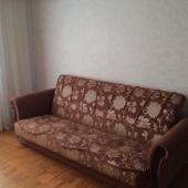 Напротив кровати есть диван
