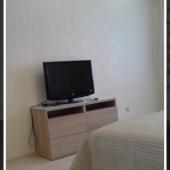 Современный ТВ на тумбе перед кроватью