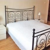 У кровати симпатичная тумбочка