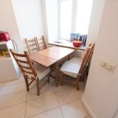 Справа в углу маленькая ниша с окном во двор, в которой примостились столик и 5 стульев