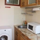 Стиральная машина стоит на кухне рядом с мойкой