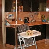 На кухне рядом с барной стойкой стоит детский стул