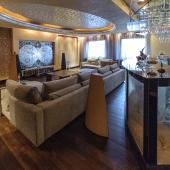 За роскошным диваном в гостиной расположилась барная стойка в виде аквариума