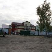 Рядом с ангаром есть прилегающая территория как парковка или открытый склад