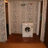 Стиральная машина примостилась в коридорном проходе между кухней и прихожей, а фото делалось из комнаты