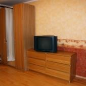 В другом углу у окна мебель: шкаф, комод, ТВ