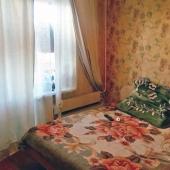 В спальной комнате стоит кровать и стенка мебельная у стены напротив
