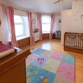 Здесь всё в основном предназначено для маленького ребенка: кровать, комоды, ковер, игрушки