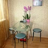 Стеклянный столик под симпатичными часами на кухонной стенке
