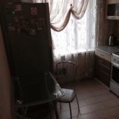 У стены столик и холодильник