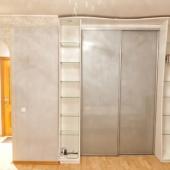 У стены стоит шкаф современной конструкции